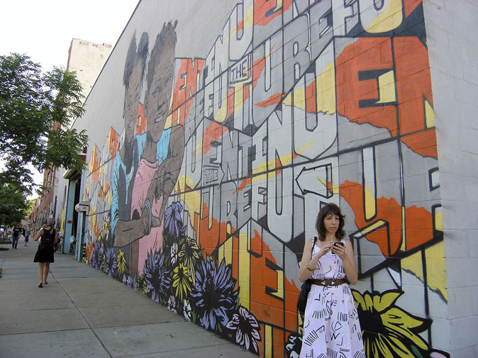 Disgruntled texting woman among the Bushwich street art. Photo by Michele Witchipoo June 2013.