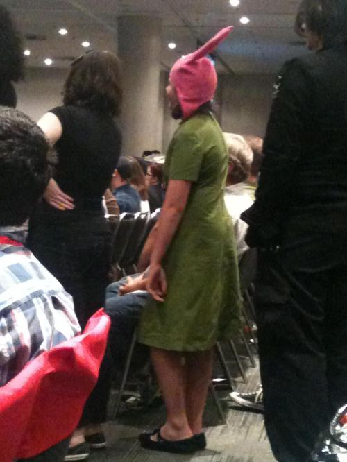 A fan waiting to ask a question at the Bob's Burgers panel at NYCC 2013. Many were dressed like the characters Louise and Tina. Photo by Michele Witchipoo, Oct. 2013.