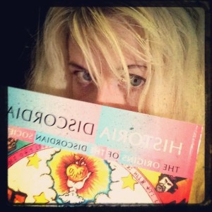 "Michele Witchipoo posing with the book ""Historia Discordia"" written by Adam Gorightly, June 2014."