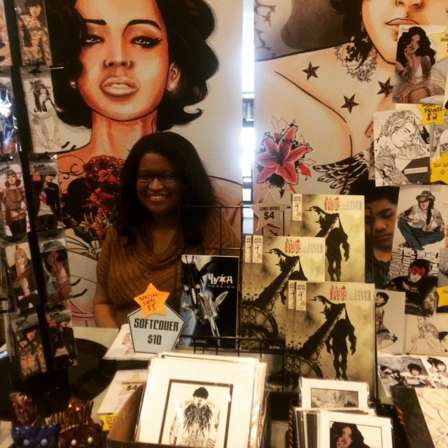 Artist Alitha E. Martinez at her table during White Plain Comic Con 2015. Photo by Michele Witchipoo.