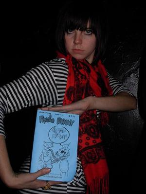Undercover WitchesBrewPress agent on a mission to get club goers to pose with a Psycho Bunny comic. Here, a WitchesBrewPress undercover agent finds a willing target to pose. Photo by Michele Witchipoo, Dec. 2008 at LIT Lounge.