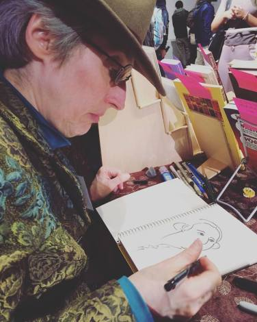 Candid shot. Sharing a table with artist E.J. Barnes. She specializes in historical comics. MoCCA Fest 2016. Photo by Michele Witchipoo, April 2016.