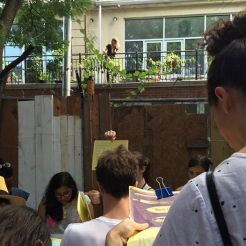 Book binding class at the Bushwick Art Book & Zine Fair 2016. July 2016. Photo by Michele Witchipoo. In the background behind the book binding class, you can see signs of the hyper gentrification happening all over NYC.
